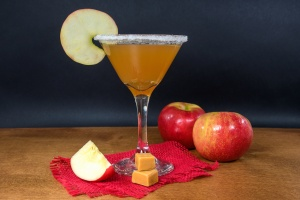 apple cider martini with caramel apples and ripe apples on wood table
